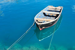 Old Boat. Old fishing boat on the transparent water surface Stock Image