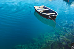 Old fishing boat. On the transparent water surface Stock Images