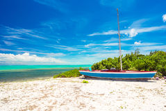 Old fishing boat on a tropical beach at the Stock Image