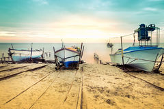 Old fishing boats laid over the sea shore. Colorful sunset above the sandy beach in Ravda, Bulgaria. Stock Images