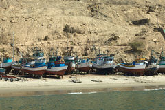 Old Fishing Boats in Mancora, Peru. MANCORA, PERU - AUGUST 17, 2013: Old wooden fishing boats and some rafts on the sandy beach on August 17, 2013 in Mancora Royalty Free Stock Image