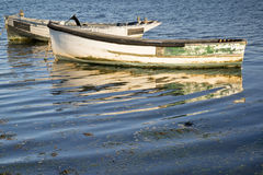 Old fishing boats reflected in calm water during Summer sunset Royalty Free Stock Photography