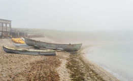 Old fishing boats on sea shore in thick fog. Early in the morning Royalty Free Stock Image