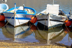 Old fishing boats tied to the shore with calm sea and reflection Stock Images