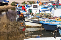 Old fishing boats tied to the shore with calm sea and reflection Royalty Free Stock Images