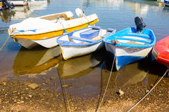 Old fishing boats tied to the shore with calm sea and reflection Stock Photo