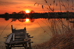 Old fishing bridge on the lake. At sunset Stock Photos