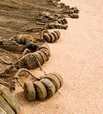 Old fishing net with bobbers floats on the golden sand and a lot of copyspace Royalty Free Stock Photo