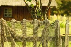 Old fishing net drying at the fence of a village house. Countryside rural outdoor background. Fishing net texture stock images