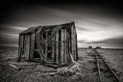 Old fishing net huts on a pebbled beach with dramatic long-expos stock photos