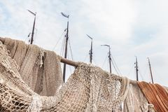 Old fishing nets in the harbor of the Dutch village of Urk. With ship masts in the background stock image