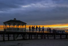 Old Fishing Pier Belmar. BELMAR, NEW JERSEY - SEPTEMBER 3 - A group of men converse at sunset on the old Belmar fishing pier destroyed during Hurricane Sandy on Royalty Free Stock Photography