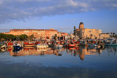 The Old Fishing Port, St Raphael 114a. Old St Raphael at night with its Cathedral and the Casino glowing with the setting sun, reflected in the sheltered waters royalty free stock photos
