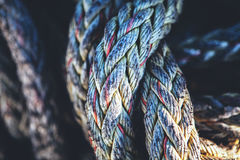 Old fishing rope texture closeup. Faded old fishing rope on the coast stock image