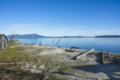 Old Fishing Shack. An old fishing shack along with motor boat, logs, and other useful things sits by the Saanich Inlet under a clear blue spring sky Royalty Free Stock Photo