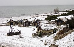 Old fishing village with stone house in winter with snow. And water a cloudy day royalty free stock photo