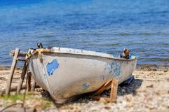 Old fishing white and blue boat tied on dock. Close Royalty Free Stock Image