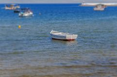 Old fishing white and blue boat tied on shore. Close Royalty Free Stock Photo