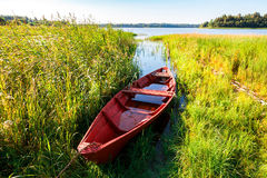 Old fishing wooden boat at the lake in summer day stock photo