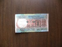 Old Five rupees India note. Obverse of green color old 5 rupees India banknote with Lion Capital of Ashoka emblem kept on wooden table stock photo