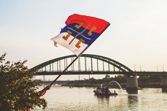Old Flag With Serbian Cross National Symbol. National symbol of Serbia-Old flag with Serbian Cross - Old bridge over river Sava in Belgrade in background stock photos