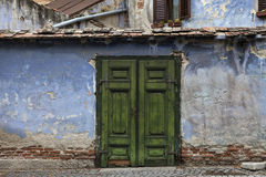 Old flaked classic green door. With blue walls - Sibiu - Romania Royalty Free Stock Images