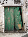 Old flaking broken green door in white wall in Fuerteventura Canary Islands Stock Image