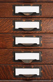 Old Flat File Drawers With Blank Labels. Vertical stack of five old oak flat file drawers with white empty tags in tarnished brass label holders Stock Photography
