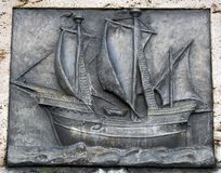 Old, flat sculpture of a ship,. Architecture detail, iron plate sculptured and put in a stone. A detail to be found in an old fountain monument situated in the Royalty Free Stock Photo