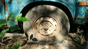 Old flat tyre of old blue vehicle in the abandoned place. Old flat tyre and rusty wheel of old blue vehicle in the abandoned place stock image