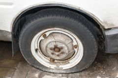 Old flat wheel of a white car with a rusty tire. Close Up old fl royalty free stock photography
