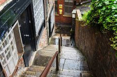 Old Flight of Stairs in a City Centre on a Rainy Day. Wet Flight of Stairs with a dividing handrails between an Old Brick Building and a Wall. Newcastle upon royalty free stock photo