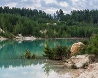 Flooded clay quarry among forest. Old flooded abandoned clay quarry surrounded by dense forest Royalty Free Stock Images