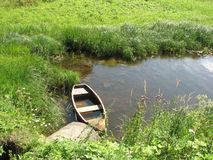 Old flooded wooden boat in a river creek near the coast, covered with grass, on a sunny summer day stock image