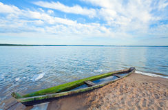 Old flooding boat on summer lake shore. Old wooden fishing boat flooding near the lake shore and summer sky behind (Svityaz, Ukraine Stock Image