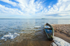 Old flooding boat on summer lake shore Royalty Free Stock Photo