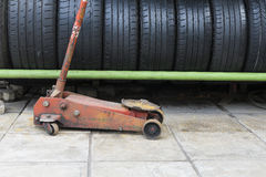 The old floor jack with the car used tire stack. Background Royalty Free Stock Photo