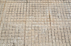 Old floor tiles small beige stone Royalty Free Stock Images