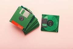 Retro floppy disks isolated on pink background. Old floppy disks isolated on pink background. Top view of magnetic retro storage devices, cutout of green Royalty Free Stock Photos