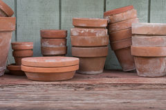 Old Flower Pots. Used terracotta flower pots rest on a gardener's rough wood bench Stock Images