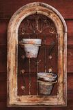 Old flowerpots' frame. Two flowerpots set in an old wrought iron element framed with wood holding on a nail on an outside wall of a house Royalty Free Stock Photo