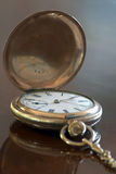 Old fobwatch. An old brass Fobwatch - open on a polished mahogany table. focus is on the center of the watch dial stock image