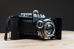 Old folding camera on a textured rustic wooden surface. Stock Photo