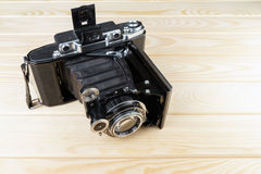 Old folding camera on a textured rustic wooden surface. Stock Photos