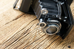 Old folding camera on a textured rustic wooden surface. Royalty Free Stock Images
