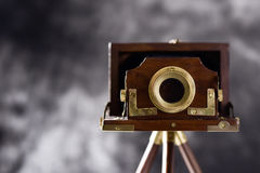 Old folding camera. An old wooden folding camera in a wooden tripod, against a gradient gray background Royalty Free Stock Photo