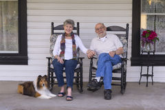 Old Folks on the Porch. A happy married couple relax on their porch in matching rocking chairs with their Shetland sheepdog by their side Stock Images