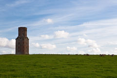 Old Folly. An eighteenth century brick folly on top of a hill, with visible blue sky and sheep Stock Photo