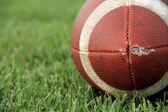 Old Football. A close up image of an old football on grass Royalty Free Stock Images
