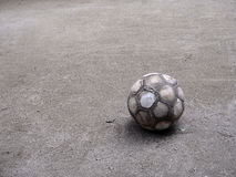 Old football ball. Very old football ball on the playground Stock Photo